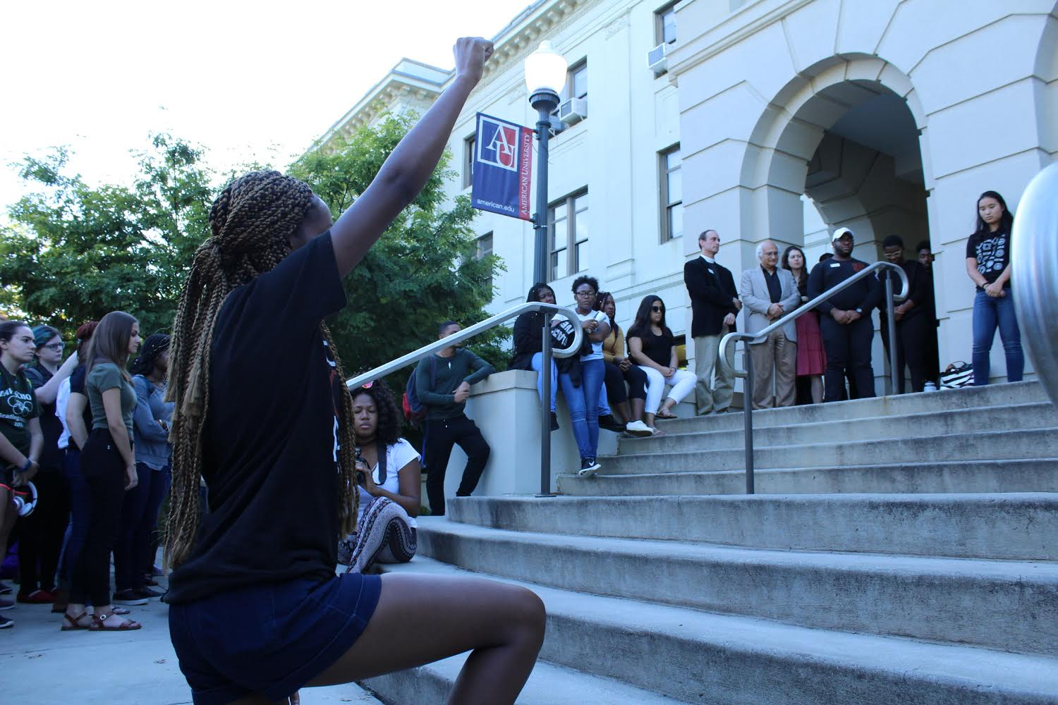 Student kneeling outside with a fist raised  in the air outside of MGC during the rally.