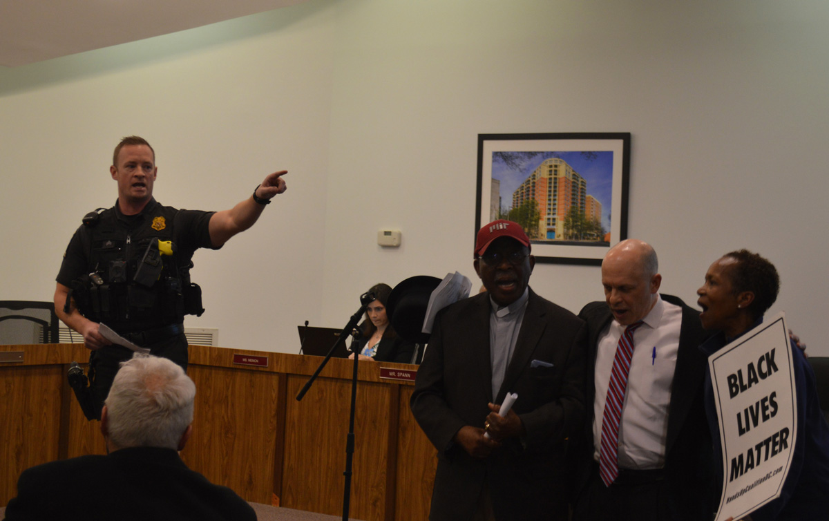 Montgomery County Police Officer, Chris Hackley, reads a statement ordering protestors to leave the public forum. Macedonia Baptist Church pastor Segun Adebayo, Somerset Mayor Jeffrey Salvin, and Lucile Perez refused to leave; they were arrested and charged with disorderly conduct.