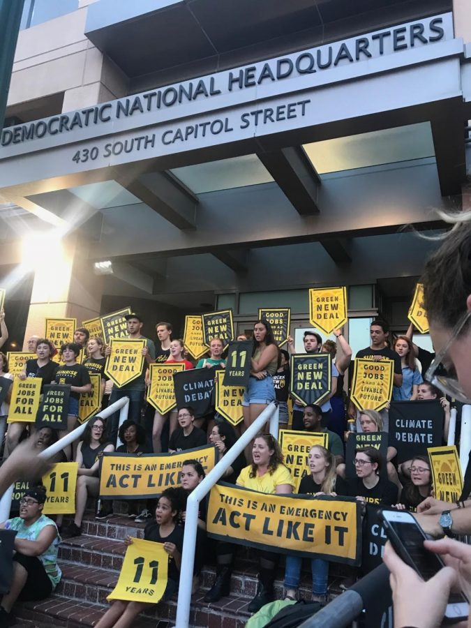 Protesters from the Sunrise Movement sing on the steps of the Democratic National Headquarters at 430 S. Capital St. They are protesting the DNC's refusal to host a climate debate. (Sasha Fernandez/AWOL Magazine).